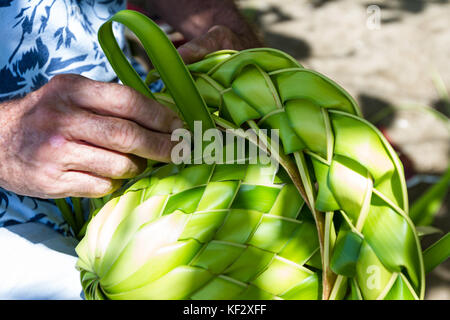 close up of a mans hands making a palm leaf hat in a beach in Costa Rica - Stock Photo