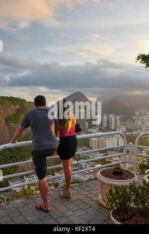 Tourists looking at Botafogo from Sugarloaf Mountain (Pao de Acucar), Rio de Janeiro, Brazil, South America - Stock Photo