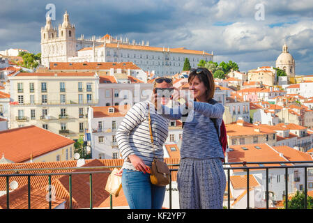 Women friends selfie, two young women take a selfie photo against the backdrop of the Alfama old town district in - Stock Photo