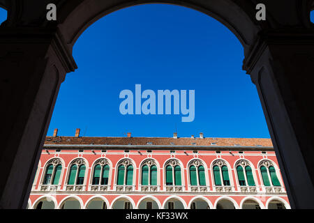 Looking towards one side of Trg Republike through an archway in Split.  The colourful open square is  surrounded - Stock Photo