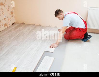 handyman laying down laminate flooring boards while renovating a house - Stock Photo