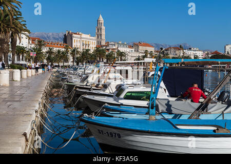 A row of fishing boats moored to the quayside at Matejuska, the Fisherman's port of Split in Croatia late one autumn - Stock Photo