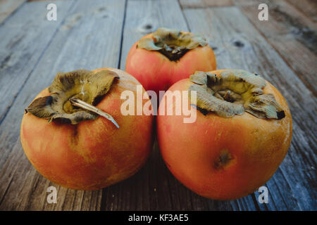 Delicious fresh persimmon fruit on a wooden board - Stock Photo