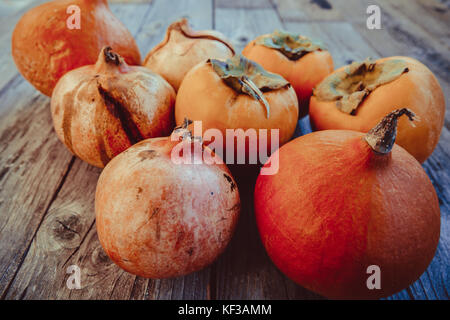 Fresh persimmon , pumpkin and pomegranate fruit on a wooden board - Stock Photo