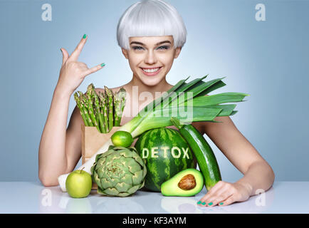 Fashion girl with an abundance of fruits and vegetables. Photo of smiling blonde girl showing gesture 'is cool'. - Stock Photo