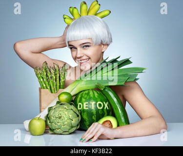 Queen of green vegetables. Photo of funny girl with an abundance of fruits and vegetables on the table. Detox concept - Stock Photo