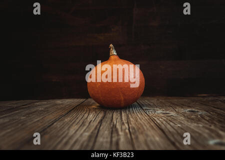 Orange pumpkin fresh raw fruit on wooden board - Stock Photo