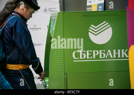 A man in a Buryat national costume takes money from an ATM of Sberbank in Russia - Stock Photo