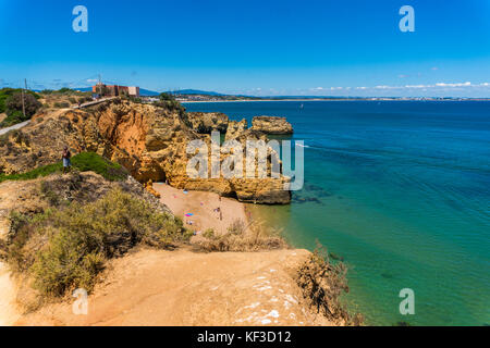 Praia, beautiful sea view with sandy beach among rocks and cliffs in Algarve, Portugal. Sunny outdoors background - Stock Photo