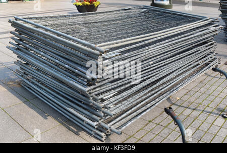 A stack of modular steel fence elements made of galvanized steel grating. Street outdoor sunny autumn day shot - Stock Photo