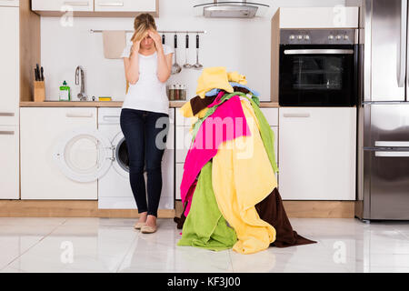 Exhausted Young Woman Standing Near Pile Of Untidy Clothes In Kitchen - Stock Photo