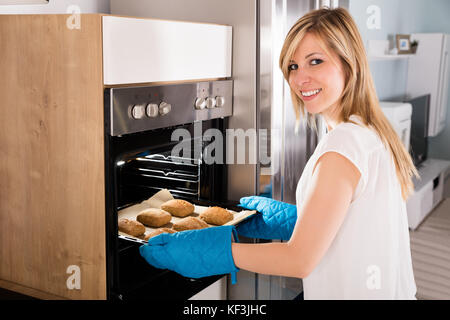 Young Smiling Woman Taking Baking Tray Out From Microwave Oven - Stock Photo