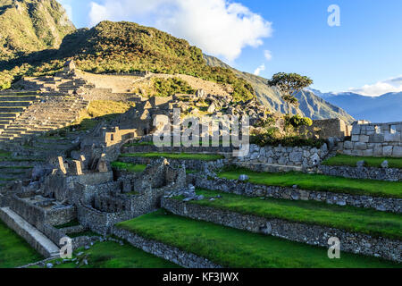 Machu Picchu green terraces and ruins with mountains in the background, Urubamba provnce, Peru - Stock Photo