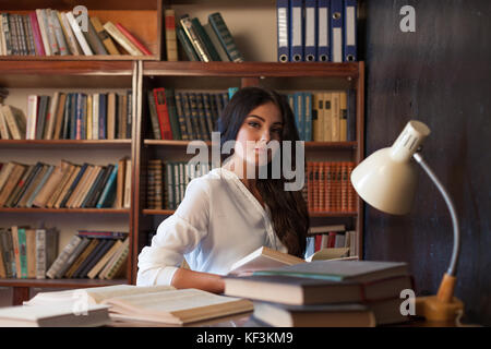 girl sitting at the table reading a book is preparing for the exam - Stock Photo