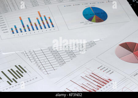 business document graph and charts on desk. - Stock Photo