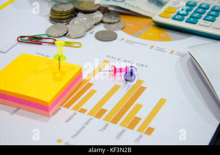 business documents on  table with mouse computer and coins and graph financial diagram. - Stock Photo