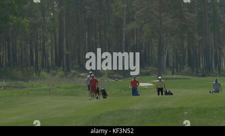 Men walking on the field for the game of Golf. Boy golfer with parents plaing golf at sunny day. Friends golfers - Stock Photo