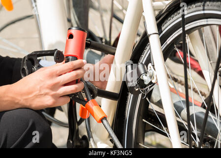 Close-up Of Businesswoman's Hand Locking Up Her Bicycle - Stock Photo