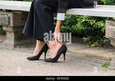 Close-up Of Businesswoman's Hand Sitting On Bench Removing High Heels - Stock Photo