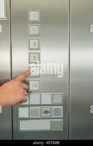 Close-up Of Female's Hand Pressing First Floor Button In Elevator - Stock Photo
