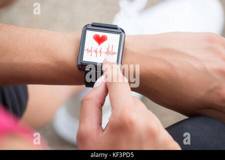 Close-up Of Human Hand Wearing Smart Watch Showing Heartbeat Rate - Stock Photo