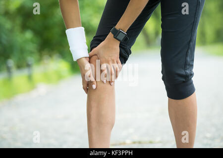 Close-up Of Female Jogger Having Pain In Her Knee - Stock Photo