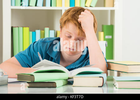 Exhausted Boy Studying In Library With Books On Desk - Stock Photo