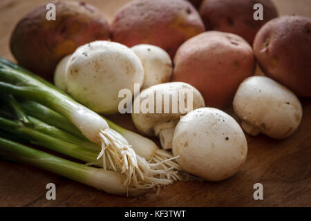 A close up image of vegetables like green onions, mushrooms, and red potatoes used in cooking. - Stock Photo