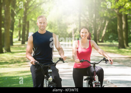 Young Happy Couple Standing With Bicycles In Park - Stock Photo