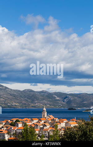 Korcula old town pictured under a mix of cloud and blue sky, neatly located on its own small peninsula jutting out - Stock Photo