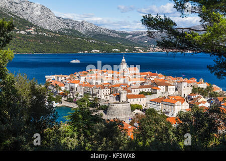 The old town of Korcula jutting out into the turquoise Adriatic on its own peninsula captured between a gap in trees - Stock Photo