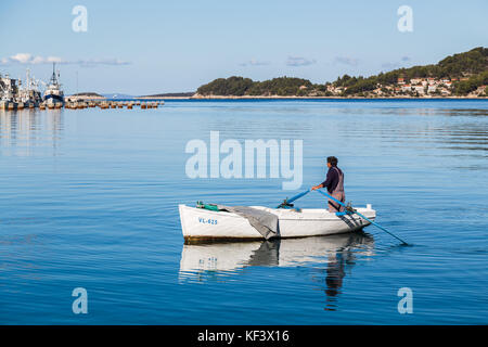 Ripples and reflections surround a man in his small white fishing boat as it approaches Vela Luka on Korcula Island. - Stock Photo