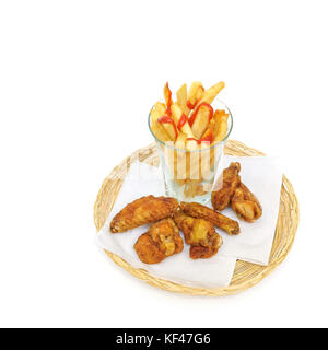 fried potato sliced as french fries in a glass and fried chicken drumsticks and wings on a paper serviettes in a - Stock Photo