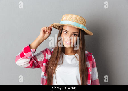 Young smiling woman in straw hat and checkered shirt, looking at camera, over gray background - Stock Photo