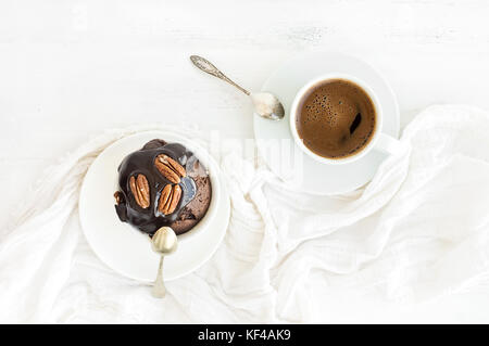 Tasty homemade brown muffin with chocolate ganache icing and pecan nuts, cup of black coffee.  - Stock Photo