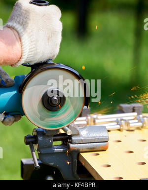 Man cutting metal with angle grinder - Stock Photo