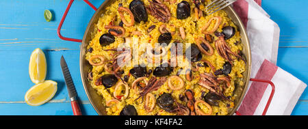 Spanish Seafood Paella in Traditional Pan on Rustic Wooden Table - Stock Photo