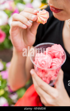 Close up beautiful girl holding plastic glass with pink air meringues in outdoors restaurant with blurred flowers - Stock Photo