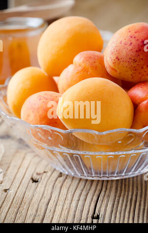 Fresh organic apricots in glass bowl on wooden board - Stock Photo