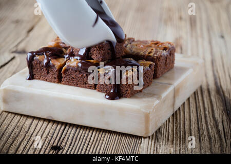 Caramel chocolate brownies with dark chocolate ganache served on marble stand - Stock Photo