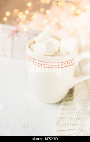 White Mug with Hot Chocolate Cocoa Drink and Marshmallows on Top. Sparkling Garland Lights in Background. Knitted - Stock Photo