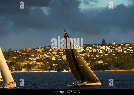 Sydney Harbour in evening light with dark clouds overhead. New South Wales, Australia. - Stock Photo