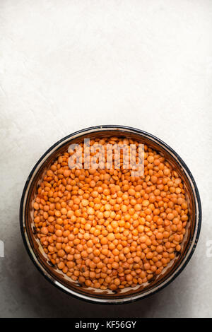 Red lentils in a clay plate on a cement background - Stock Photo