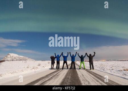 Hikers admire the Aurora Borealis, Gymsøya, Lofoten Islands, Norway - Stock Photo