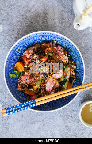 Beef fillet stir fry with courgette, radishes, bok choi and rice noodles - Stock Photo
