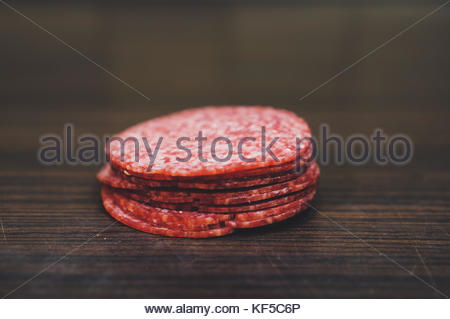Pile of fresh salami slices on wooden table in soft focus - Stock Photo