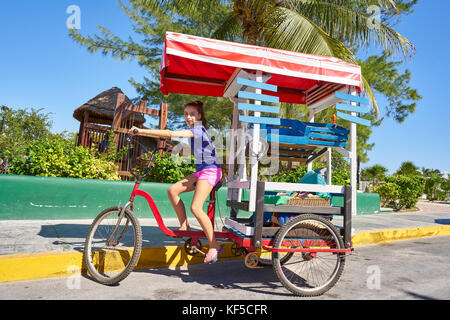 Young girl with caribbean bicycle shop on tricycle of Mexico - Stock Photo