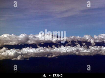 Mount Kilimanjaro peeking above the clouds. - Stock Photo