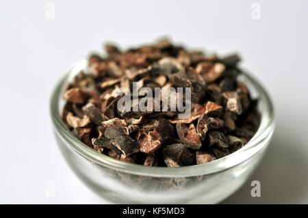 Raw cacao bean (Theobroma cacao) nibs in a glass bowl, isolated on white. Nutritious dietary supplement rich in minerals, vitamins, and fiber.