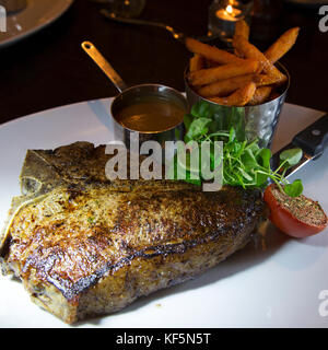T-bone steak of meat from a British-raised Hereford cattle. The dish is served with a pepper sauce and sweet potato - Stock Photo